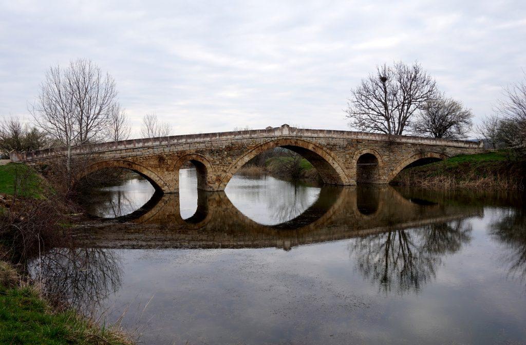 Гледка към римския мост над река Осъм с огледално отражение във водата.