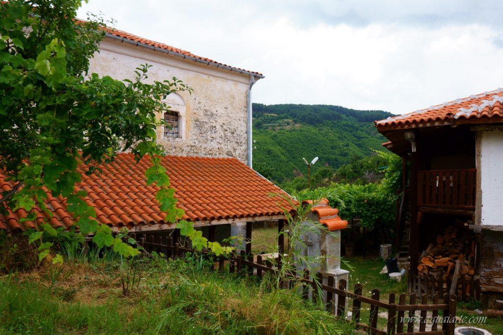 Гледка към кръста от задната част на чешмата и към сградата на килийното училище на Чуриловския манастир